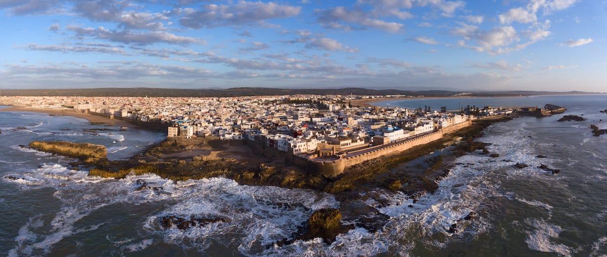 Ciudad amurallada sobre acantilados vista desde el mar.