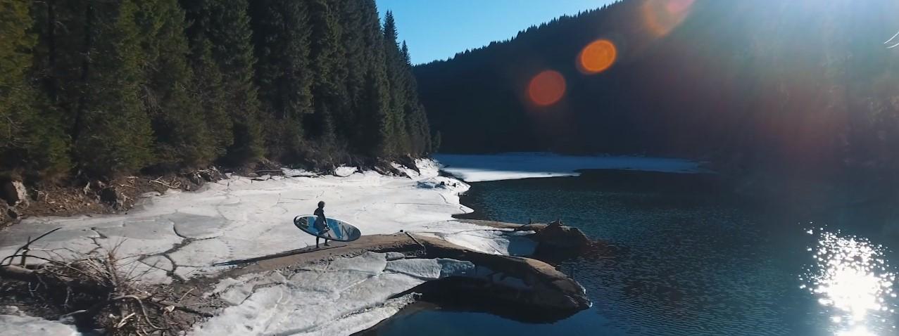 hombre con tabla de surf en lago de alta montaña