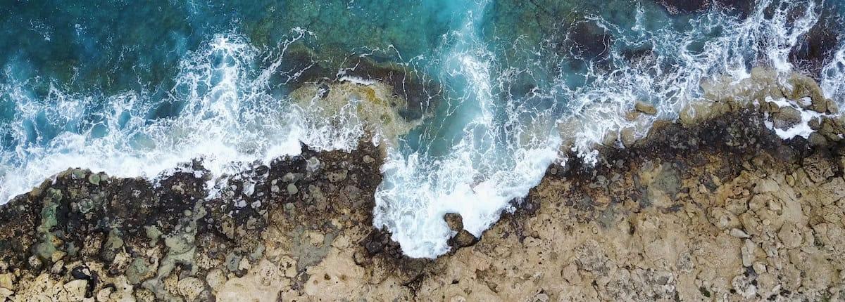 Mar color turquesa con espuma blanca rompiendo contra costa escarpada de rocas color arena.