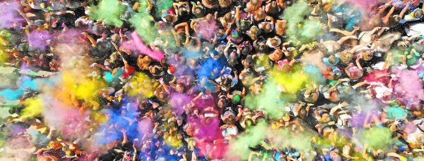 personas lanzando polvo de colores en el festival holi colors
