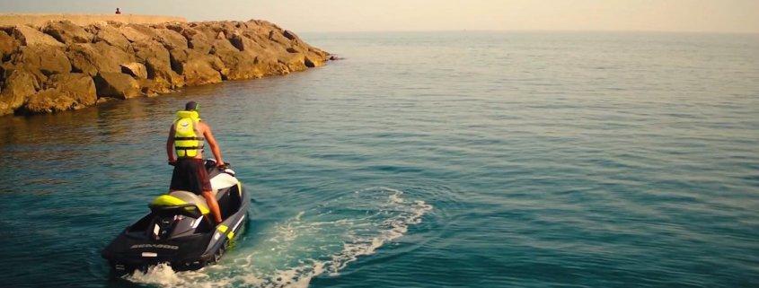 hombre de pie en moto de agua en el mar con espigon de fondo
