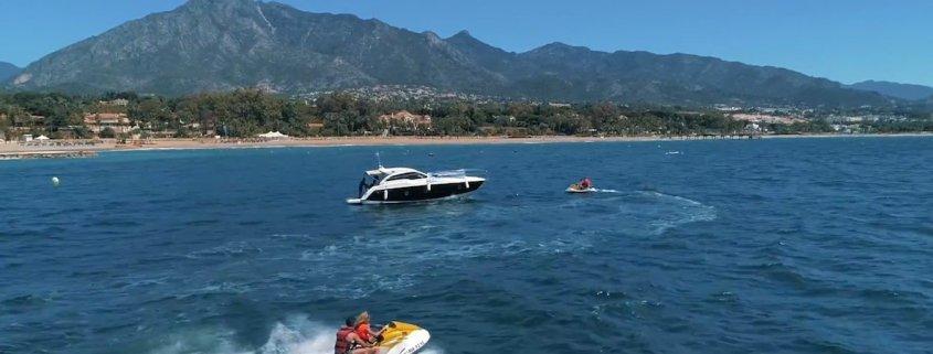 yate con motos de agua en el mar con montaña de fondo