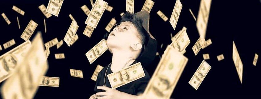 niño con gorra y gafas mirando una lluvia de billetes de dolar