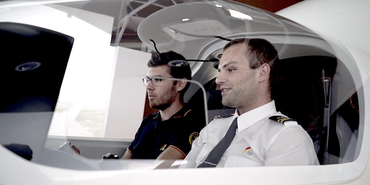 Toma de dos alumnos en simulador de vuelo para vídeo corporativo de escuela de pilotos.
