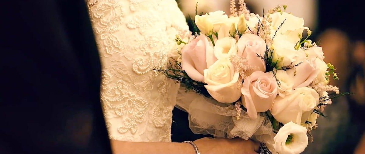 Ramo de novia sujetado por ella, con detalle de pedrería del vestido de novia.