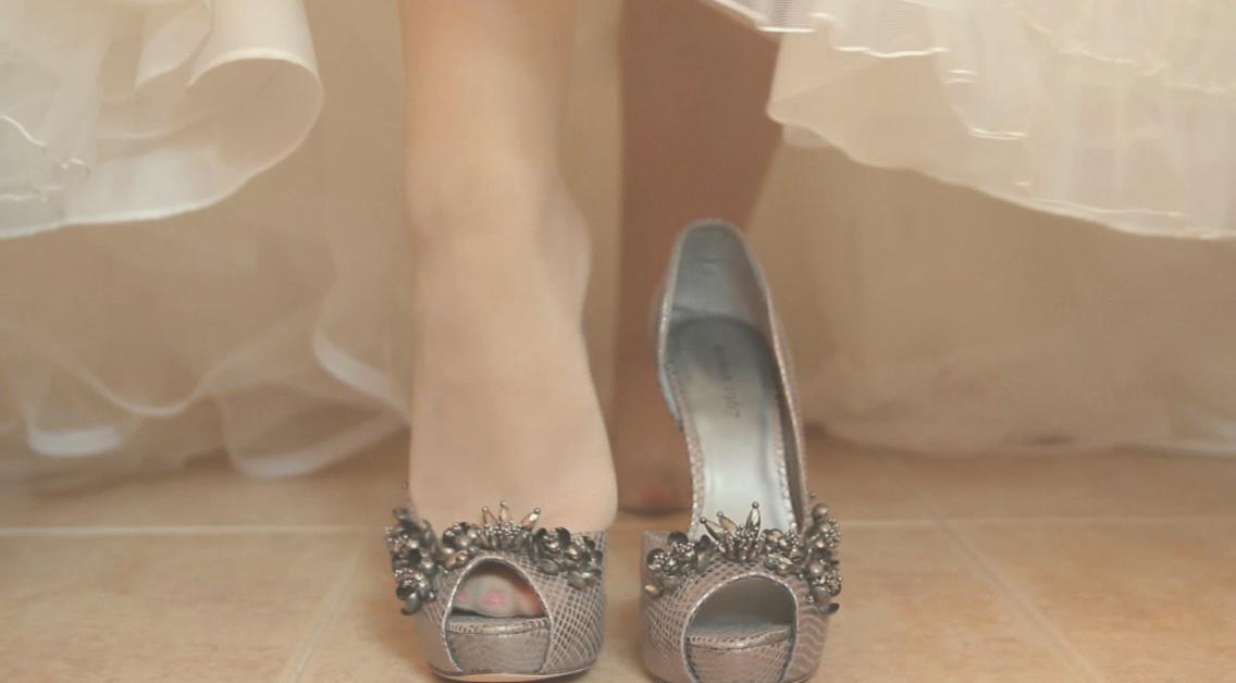 Novia poniéndose los zapatos con vestido antes de la boda